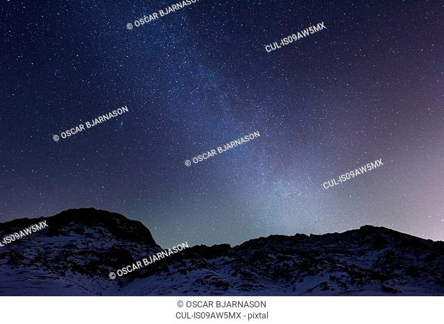 Rugged mountain on snow covered landscape underneath starry night sky, Kleifarvatn, Iceland