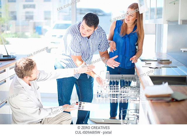 Couple and salesman looking at dishwasher in kitchen showroom