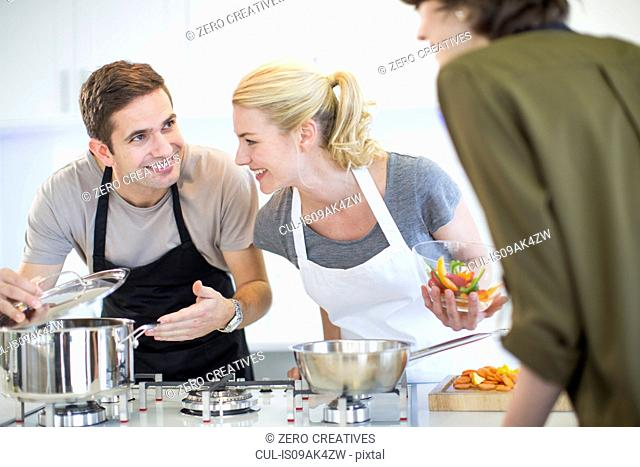 Mid adult man and friends preparing food in kitchen