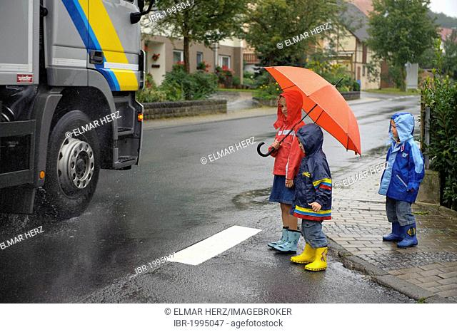 3 children, 3 to 7 years, crossing the main road in the rain, Assamstadt, Baden-Wuerttemberg, Germany, Europe