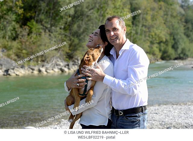 Mature couple with a dog at the river Isar, Upper Bavaria, Germany