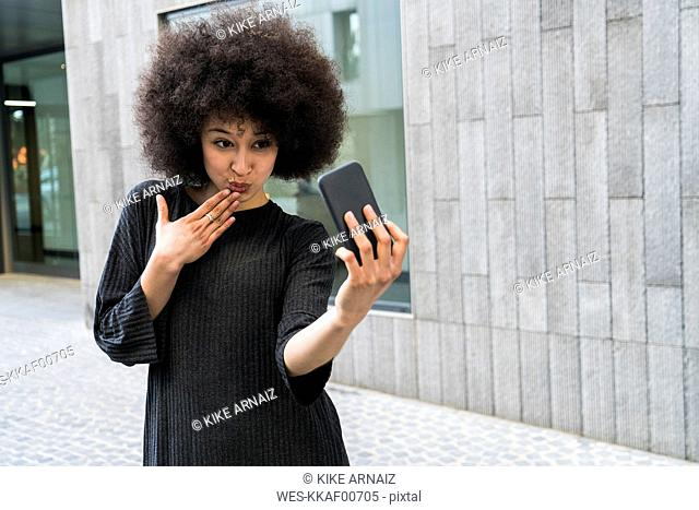 Portrait of young woman taking selfie with smartphone