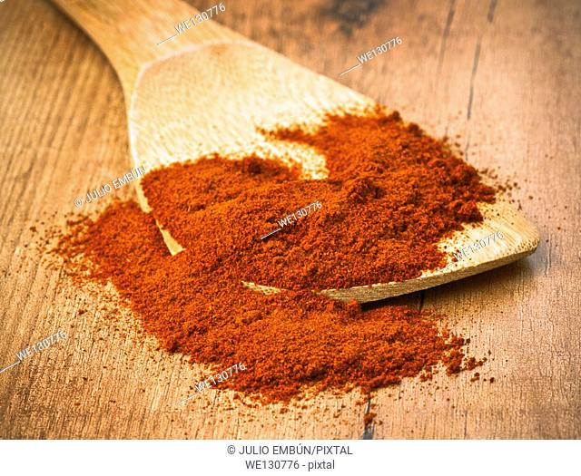 paprika on wooden spatula on rustic wooden base