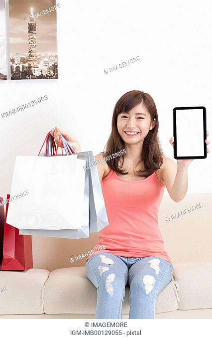 Young woman holding shopping bags and touch pad with smile
