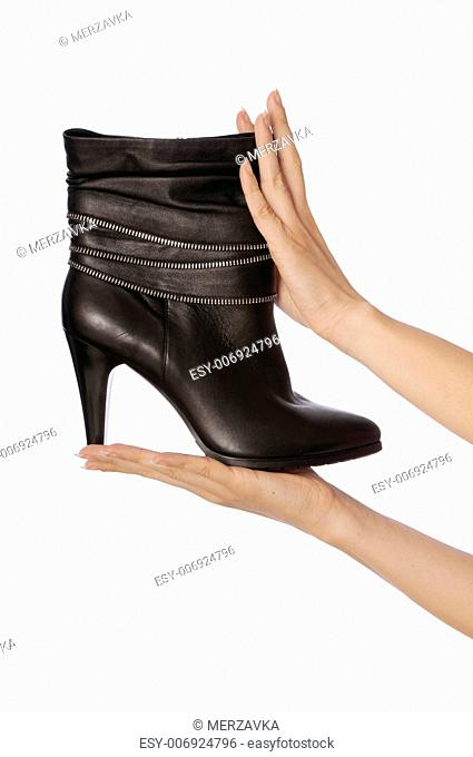 Black female boots in hands at the saleswoman