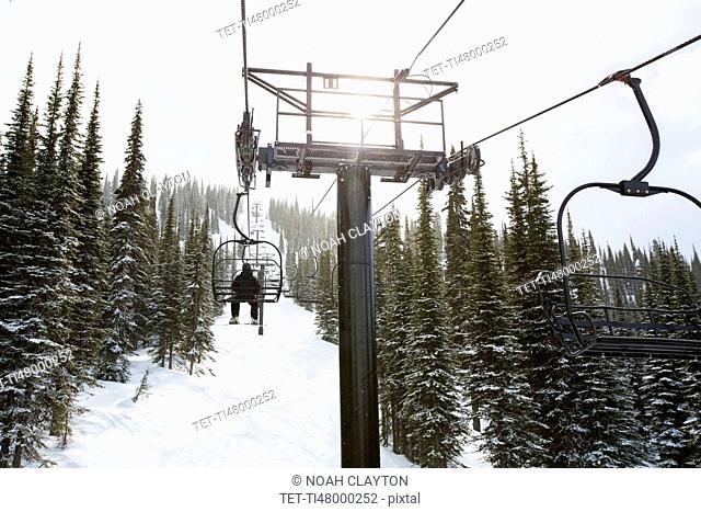 Man in ski lift, rear view