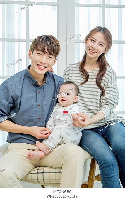 Smiling parents posing with their baby