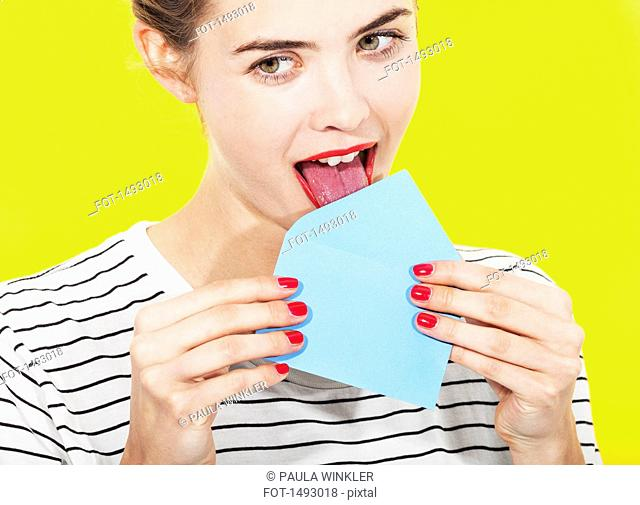 Beautiful woman licking blue envelope against yellow background