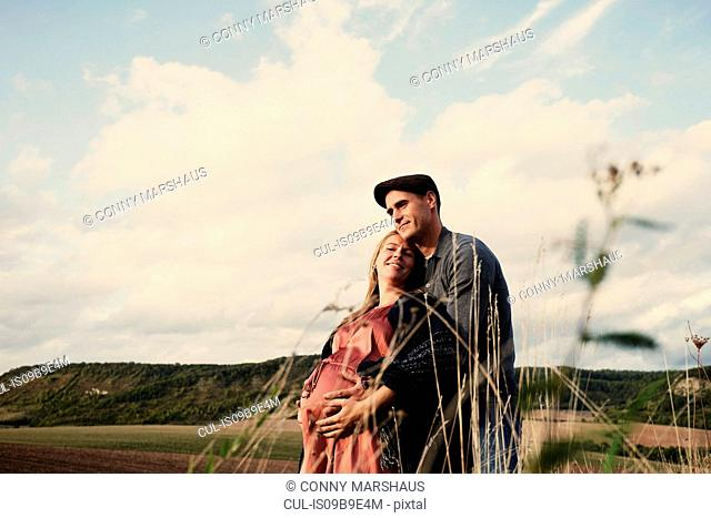 Portrait of happy pregnant mid adult couple in fields