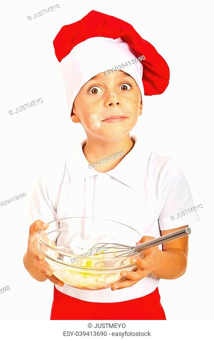 Amazed chef boy with messy face of flour holding dough isolated on white background