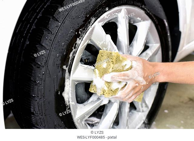 Car cleaning, man cleaning car, washing the alloy wheel