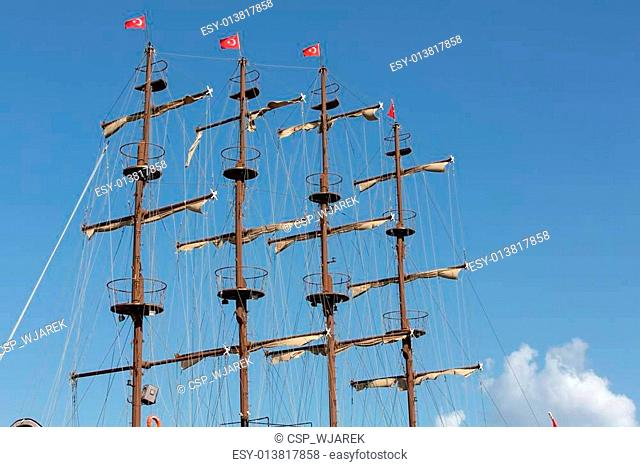 Masts and sails of huge sailing boat against the background of blue sky