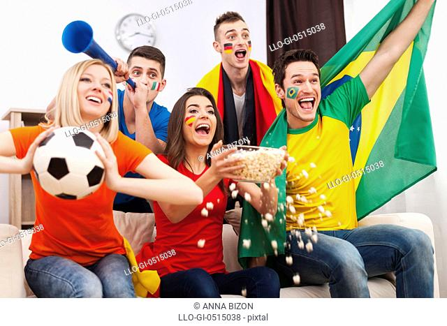 Friends of different nations celebrating goal of favourite team. Debica, Poland