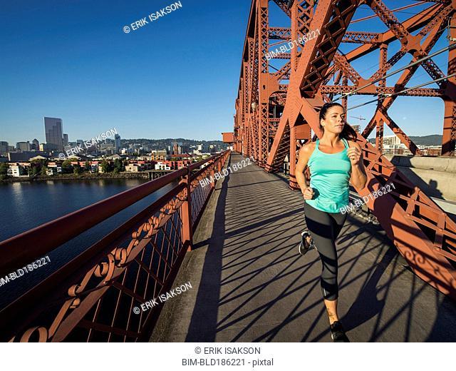Caucasian woman jogging on urban bridge, Portland, Oregon, United States