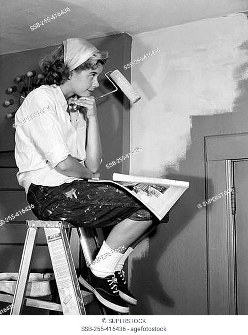 Woman sitting on ladder with paint roller