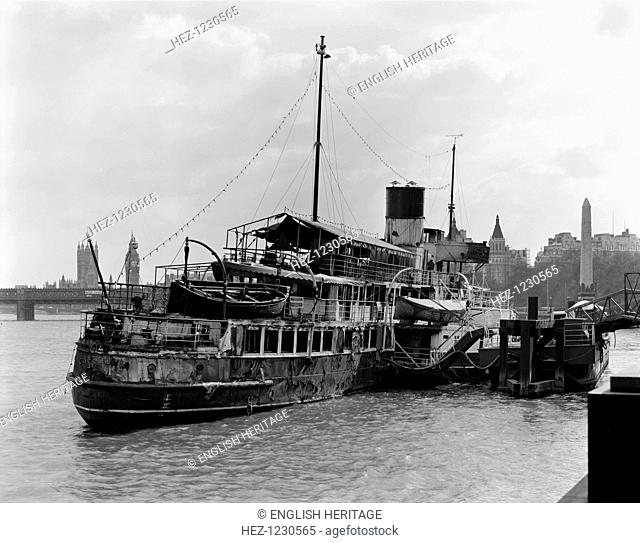 The Old Caledonia, derelict and fire damaged, moored on the Victoria Embankment, London, 1980. Landmarks visible in the background include Cleopatra's Needle