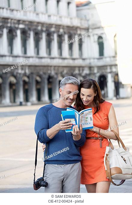 Smiling couple looking at guidebook in St. Mark's Square in Venice