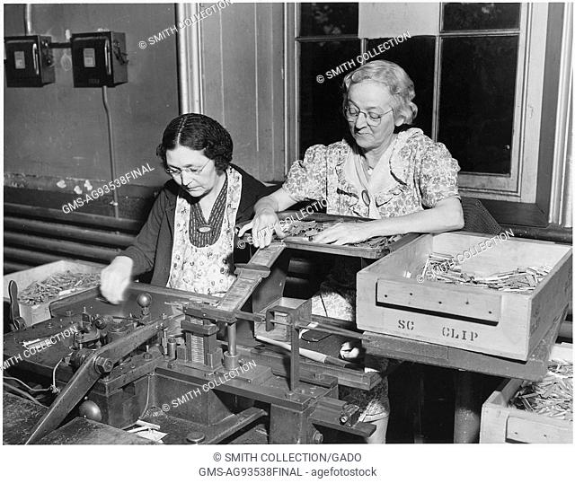 Two women working on the clip spring and bolt assembly for the .3 caliber cartridges at the Frankford Arsenal in Philadelphia, Pennsylvania, 1940