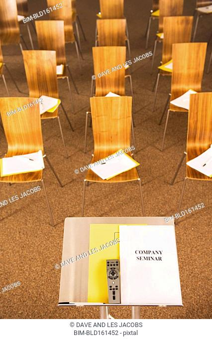 Empty chairs and podium with pamphlets in presentation room