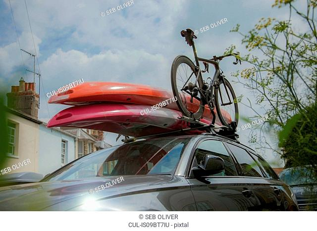 Car with surfboards and bicycle on roof rack