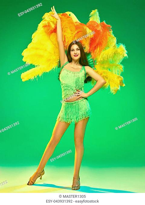 young beautiful dancer with carnival feather and fringe posing on studio background