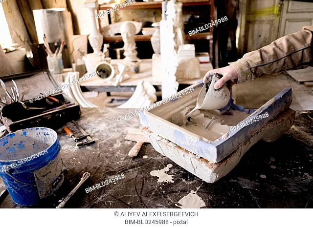 Caucasian artist pouring plaster into mold