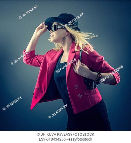 Urbane mature woman wearing a sunglasses and hat, studio shot