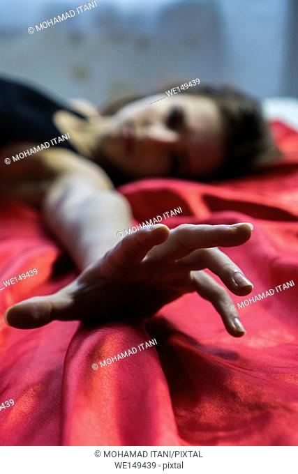 Young woman laying down in bed hand reaching out