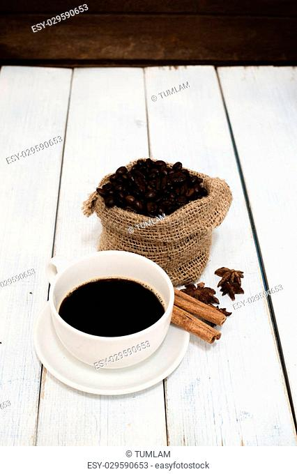 Black coffee in coffee cup and beans with cinnamon sticks on the table Wood