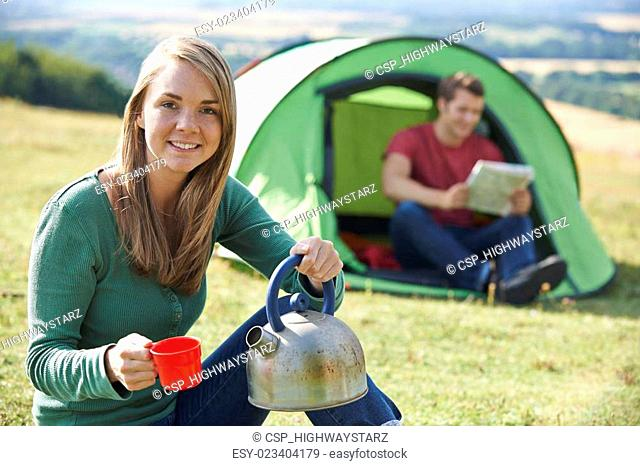 Couple Making Hot Drink Whilst Camping In Countryside