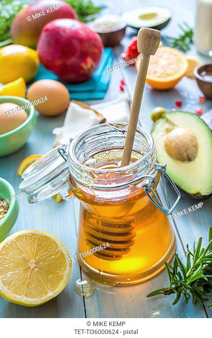 Jar of honey with dipper and fresh fruits and herbs