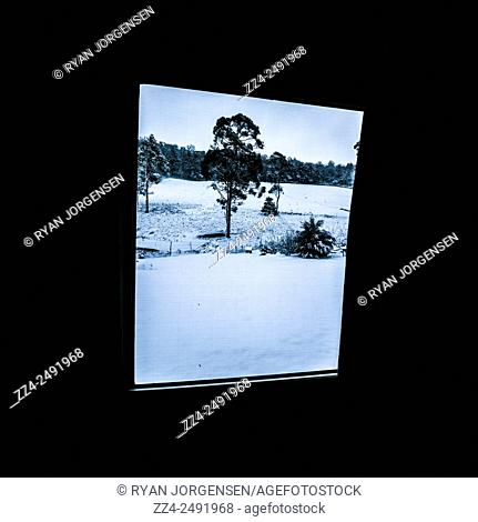 Black and blue snow landscape taken from the interior of a rural Australian home with black frame copyspace. Pelham, Tasmania, Australia