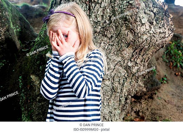 Girl peeping through covered eyes