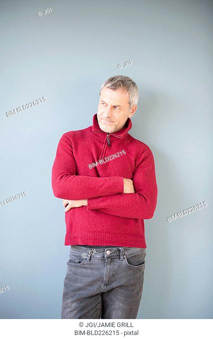 Older Caucasian man wearing sweater leaning on wall