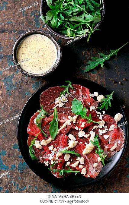 Beef carpaccio on black plate with mustard and parmesan sauce, cheese and arugula over old dark texture background. Top view with space for text