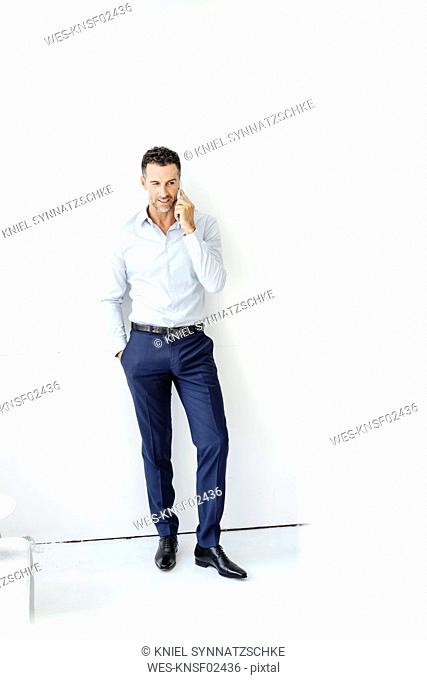 Businessman standing at a wall talking on cell phone
