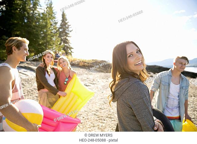 Portrait smiling woman with friends on sunny beach