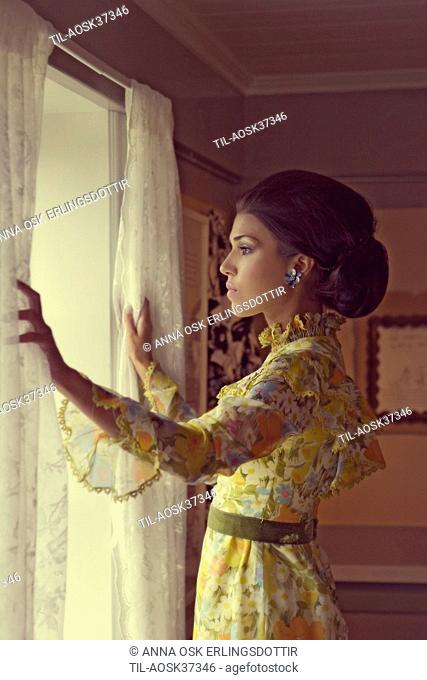 Lone female figure wearing period yellow summer dress looking out of window