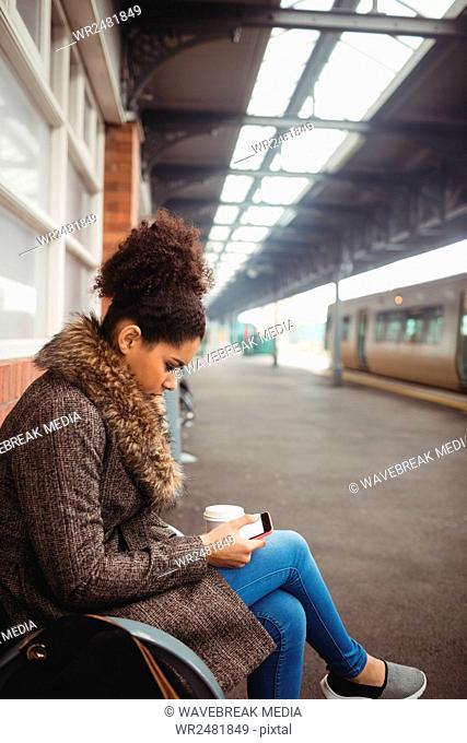 Woman using phone at train station