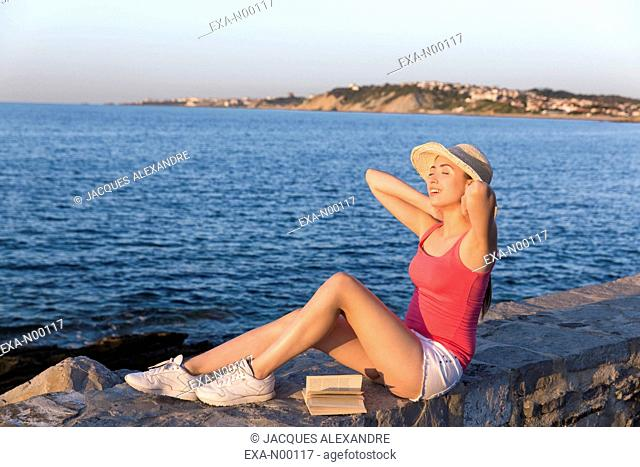 Woman reading a book at seaside