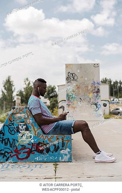 Young man in skatepark sitting on bench, listening music
