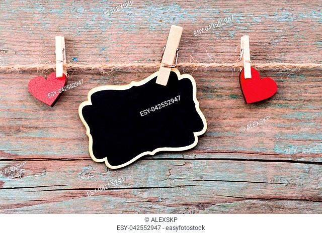 A red heart shape and a blackboard with Happy Valentine's Day text on rustic wooden table