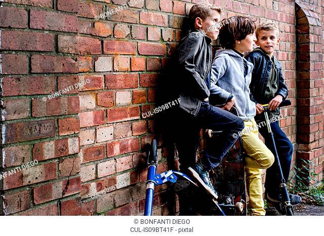 Boys leaning against brickwall