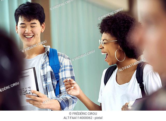 Students laughing together in corridor