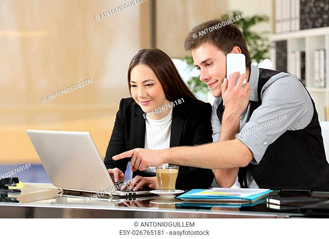 Two coworkers working together online giving instructions with a laptop and calling on the phone in a desk at office