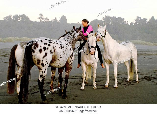 Woman riding horse bareback on beach with other horses. US Pacific coastline. California