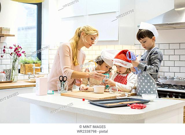 A woman and three children working together, making a gingerbread house, and icing the gingerbread