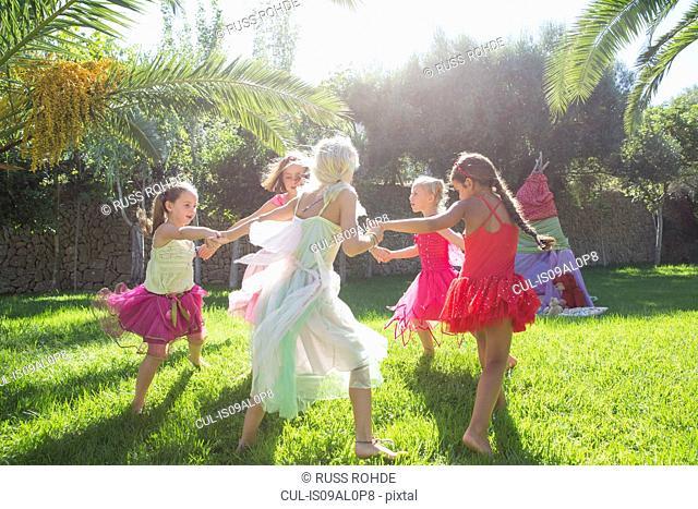 Five energetic girls in fairy costume playing in garden