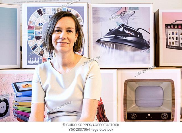 Zoetermeer, Netherlands. Portrait of an adult caucasian woman sitting in front of images, representing vintage industrial designed household items