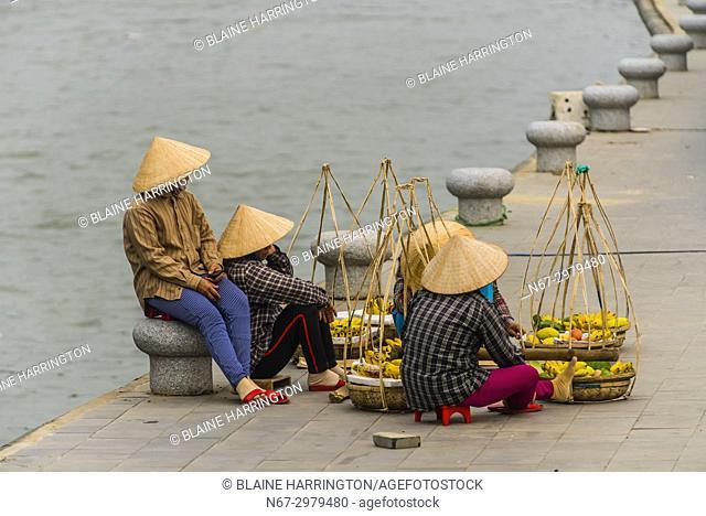 Street vendors taking a break along the Thu Bon River, Hoi An, Vietnam